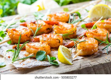 Seafood. Shellfish. Grilled fried Shrimps Prawns on wooden skewers with spices and fresh herbs on wooden rustic cutting table on wooden background. Srimps prawns brochette kebab. Barbecue srimp