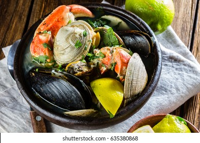 Seafood shellfish soup of mussels, crabs, clams and other shellfish served in clay bowls. typical chilean dish Paila marina or Mariscal. Top view.