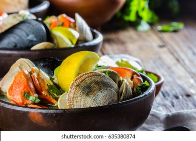 Seafood shellfish soup of mussels, crabs, clams and other shellfish served in clay bowls. typical chilean dish Paila marina or Mariscal. Top view
