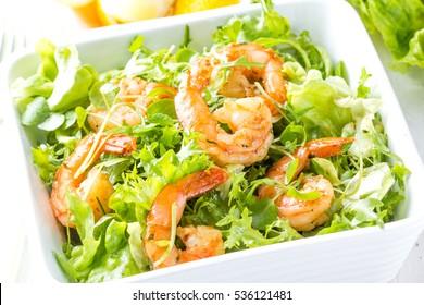 Seafood shrimp prawns. Shrimp lettuce salad in white bowl with lemon rosemary arugula on wooden white background. Healthy food or diet concept.