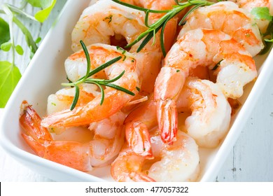 Seafood. Shrimps prawns with fresh herbs and lemon on white plate on wooden white background