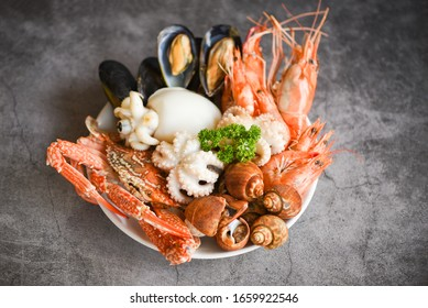 Seafood shrimps prawns squid mussels spotted babylon shellfish crab  on plate and dark background / Cooked food served seafood buffet concept