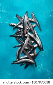 Seafood. Small sea fish, anchovies, sardines on the blue background. Fish pattern