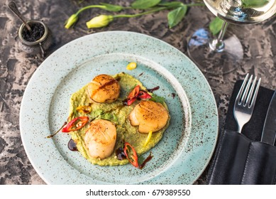 Seafood snack -  Sea scallops and vegetables, glass of wine and flowers. Close-up on a black table. Healthy fresh food.