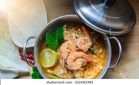 Seafood Suki in broth and vegetable Thai herb with spicy soup in stainless bowl on a wooden table. Thai traditional food. Selective focus/still life image.
