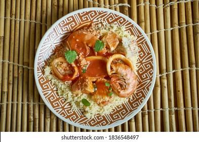 Tagine mit Meeresfrüchten - marokkanischer Eintopf, serviert über einem zestvollen Mandelcouscous