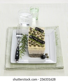 seafood terrine with capers olives with rosemary on a white square plate striped napkin