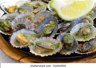 Seafood.Grilled limpets served with lemon.Lapas grelhadas.Madeira's traditional dish and a typical snack on Canary Islands.