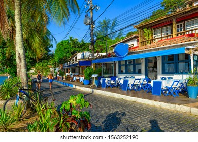 Seafront of Brigitte Bardot with palms and tables of restaurant in Buzios, Rio de Janeiro. Brazil. Cityscape of Buzios.