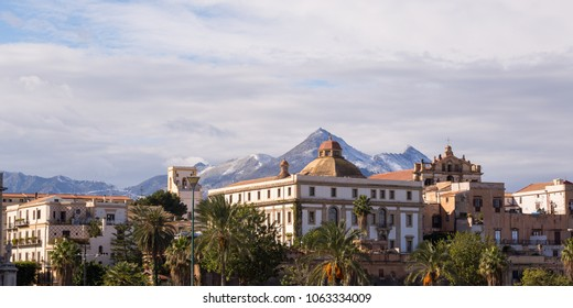 Seafront buildings in Palermo with snowy mountains in the background. the image was taken in January 2017.