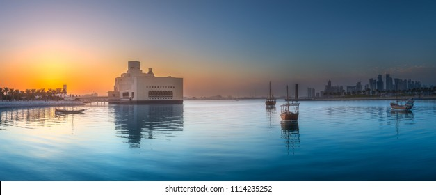 Seafront of Doha park and East Mound-Skyline view during purple sunset with boats, Qatar.