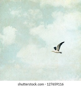 A seagull and clouds on a vintage paper background with grunge textures and grain.