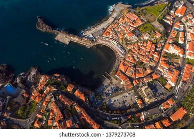 Seagull view to Camara de Lobos Madeira island Portugal. Aerial drone top view to fishermen village on Madeira. Beautiful Camara de Lobos bay, red roofs, white houses. Camara de Lobos village Madeira.