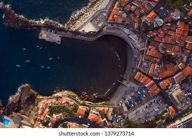 Seagull view to Camara de Lobos Madeira island Portugal. Aerial drone top view to fishermen village on Madeira. Beautiful Camara de Lobos bay from bird perspective. Camara de Lobos village Madeira.