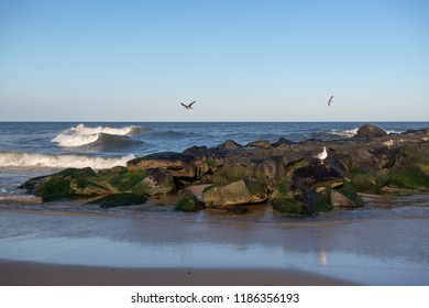 Seagulls with waves fly over this rock jetty in Avon by the Sea along the New Jersey coastline.