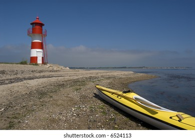 Sea-Kayak beached near small red and white light house. Jutland, Denmark