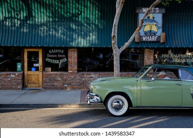 Seal Beach, CA / USA - March 24 2019: Street view with a studebaker antique car and a restaurant in Seal Beach
