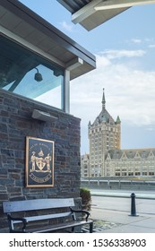 The Seal of The City of Albany or The coat of arms of Albany, which is the heraldic symbol representing the city of Albany (Assiduity) in Forground and the D&H bUilding in Background.