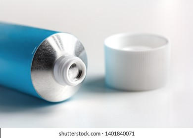 sealed tube of ointment on a white background with an open lid
