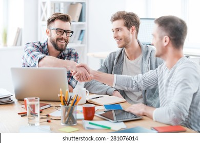 Sealing a deal. Business people shaking hands while sitting at the desk in office