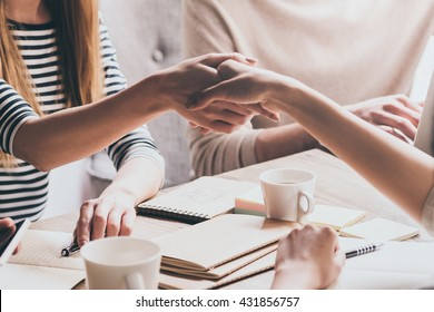 Sealing a deal. Close-up of two businesswomen shaking hands while sitting at the desk with man in the background