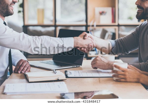 Sichern eines Deals. Seitenansicht, Nahaufnahme von zwei jungen Männern, die sich am Holzschreibtisch die Hände schütteln