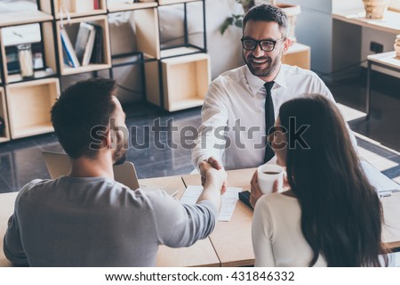 Sealing a deal. Top view of two men sitting at the desk and shaking hands while young woman looking at them and smiling