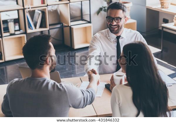 Sichern eines Deals. Draufsicht von zwei Männern, die am Schreibtisch sitzen und Händchen schütteln, während junge Frau sie anschaut und lächelt