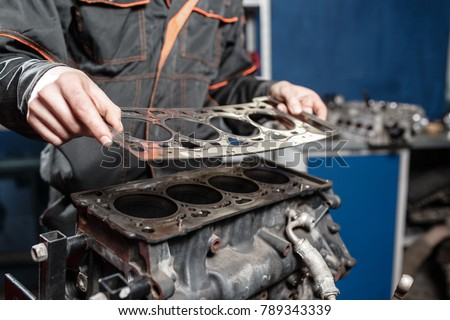 sealing gasket in hand  the mechanic disassemble block engine vehicle  engine  on a repair