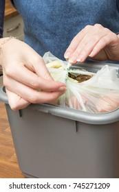 Sealing a plastic bag full of food scraps in a waste bin