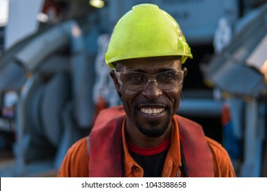 Seaman AB or Bosun on deck of vessel or ship , wearing PPE personal protective equipment - helmet, coverall, lifejacket, goggles. He is smiling. Safety at sea