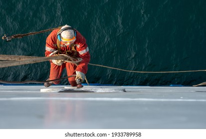 Seaman ship crew working aloft at height derusting and getting vessel ready for painting. Boat maintenance. - Shutterstock ID 1933789958
