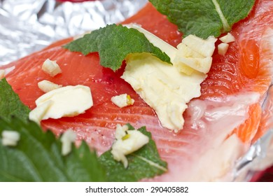 Seaman-trout with garlic, mint and nettle close-up on red table