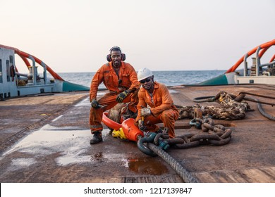 Seamen AB or Bosun on deck of offshore vessel or ship , wearing PPE personal protective equipment - helmet, coverall, lifejacket, goggles. They prepare towing wire