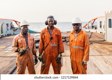 Seamen crew AB or Bosun on deck of offshore vessel or ship , wearing PPE personal protective equipment - helmet, coverall, lifejacket, goggles. Towing team