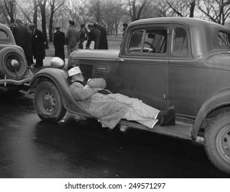 Seamen protest against the Copeland Safety-At-Sea Act. Jan. 18, 1937. One striker takes a nap on an auto running board as his mates protest.
