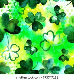 A seamless background pattern with vibrant hand drawn watercolour shamrocks on a green texture