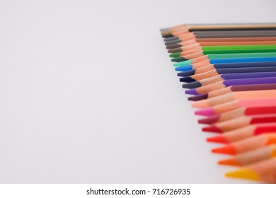 seamless colored pencils row on white painting paper background.