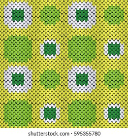 Seamless knitting geometrical pattern with symmetrical square cells in green yellow and white colors as a knitted fabric texture