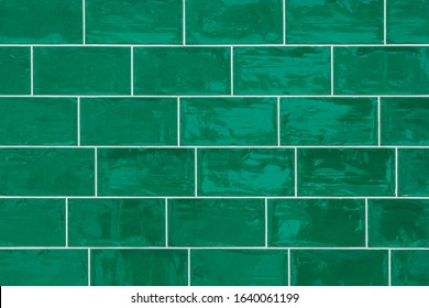 Seamless old and crooked shiny green ceramic tiled background texture.