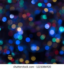 seamless pattern background, colorful bokeh with out of focus blurry glitter lights against black