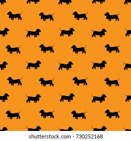 Seamless pattern with black dogs silhouettes - Dachshund on orange background. Animal design. Raster version