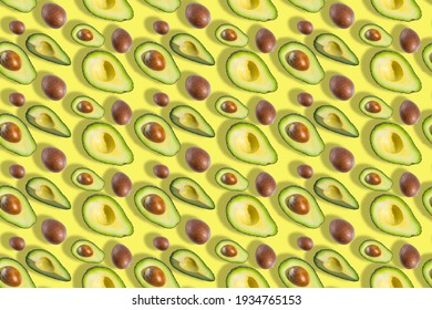 Seamless pattern of fresh ripe green avocado fruit halves with bones isolated on yellow background. Top view. Banner. Flat lay composition. Creative avocado background