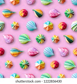 Seamless pattern of multicolored meringues. Colorful little meringue cakes on a pink pastel background. Appetizing meringues. Arrangement of cakes in several rows. View from above.