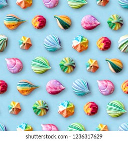 Seamless pattern of multicolored meringues. Colorful little meringue cakes on a blue pastel background. Appetizing meringues. Arrangement of cakes in several rows. View from above.