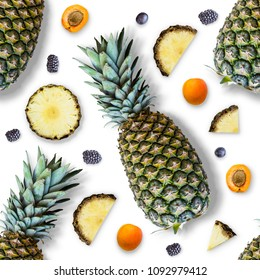 Seamless pattern of pineapple, its slices and berries on a white background. Summer background. Flat lay, top view. Minimum summer concept.