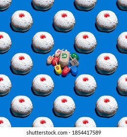 """Seamless pattern with sufganiya and wooden dreidels for Jewish holiday Hanukkah on blue background. Hebrew letters on dreidels say: """"Great Miracle Happened Here""""."""