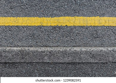 Seamless single yellow line on a grey roadside curb shot from above.