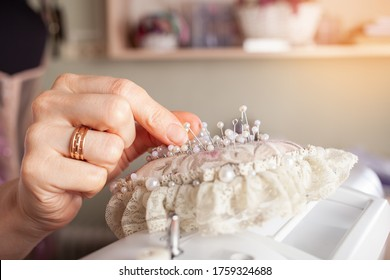 The seamstress in the atelier pulls out a pin from a beautiful lace cushion of a needle. A woman sews clothes with her own hands. Pink pad with pins on a brown table.