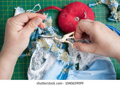 seamstress cuts the thread with sewing scissors